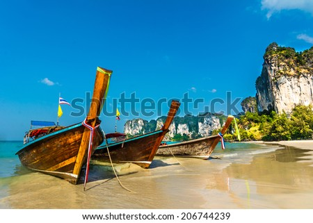 Longtail boats on Railey beach, Krabi, Thailand. Beautiful scenery with blue water and limestone cliffs - stock photo