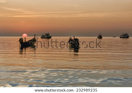 Longtail boats on seashore at sunset, Thailand. - stock photo