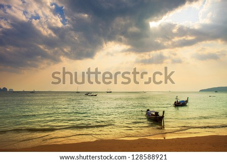 Longtail local boat on the beach at sunset time. - stock photo