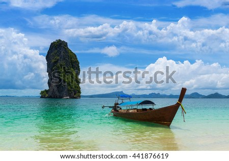 Longtil boat on heavenly beach and amazing clouds on blue sky background.