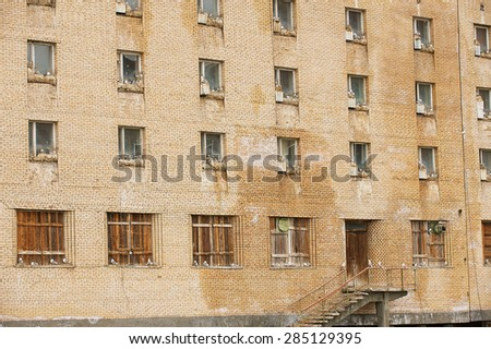 LONGYEARBYEN, NORWAY - SEPTEMBER 03, 2011: Birds sit on nests in the windows of the building in the abandoned Russian arctic settlement Pyramiden, Norway. - stock photo
