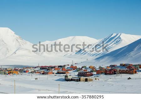 LONGYEARBYEN, SPITSBERGEN, NORWAY - 03 APRIL, 2015: Small town Longyearbyen among snow-capped mountains of the Norwegian archipelago of Svalbard. - stock photo