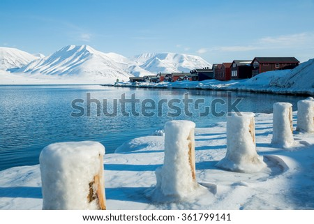 LONGYEARBYEN, SPITSBERGEN, NORWAY - APRIL 08, 2015: Small town on the shores of the Arctic ocean among snow-capped mountains of the Norwegian archipelago of Svalbard. - stock photo