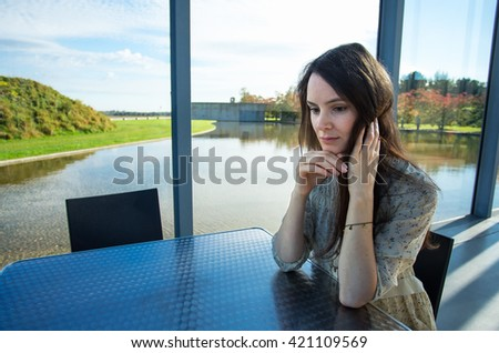 Lonly, thoughtful, sad  woman at the window - stock photo