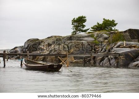 Lonly wooden boat in rain weather - stock photo