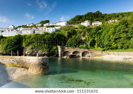 Looe harbour and river Cornwall England, with turquoise clear sea on a sunny summer day and town on the hillside - stock photo