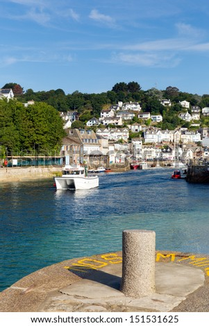 Looe harbour Cornwall England with boat blue sea on a sunny summer day - stock photo