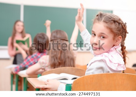 Look at me. Pupil raising hand turned away from teacher in classroom. - stock photo