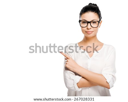 Look at that! Beautiful young woman pointing away and looking at camera while standing against white background - stock photo