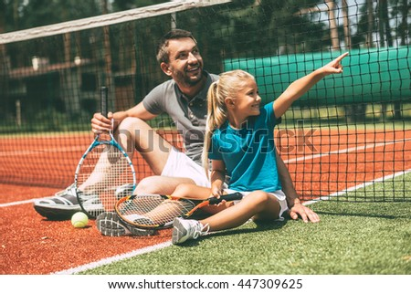 Look at that! Cheerful father and daughter leaning at the tennis net and looking away with smiles while both sitting on tennis court