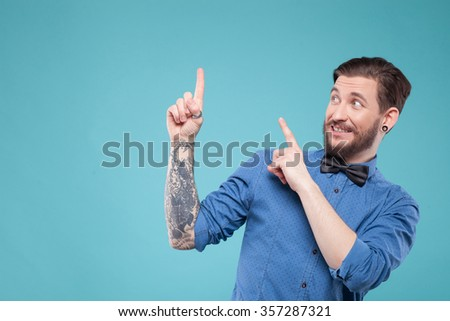 Look at that. Cheerful hipster is pointing finger sideways and laughing. Isolated and copy space in left side - stock photo