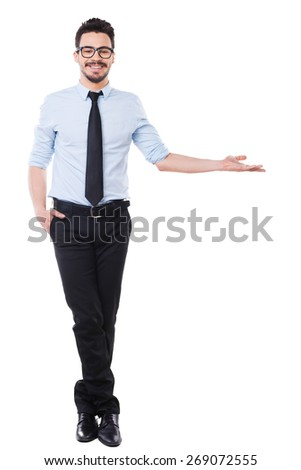 Look at that! Full length of handsome young man in shirt and tie pointing away and smiling while standing against white background - stock photo