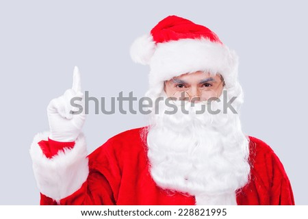 Look at that! Traditional Santa Claus pointing up while standing against grey background