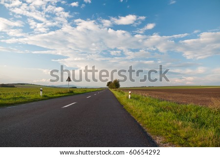 Look at the asphalt road in a beautiful sunny autumn day - stock photo