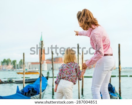 Look at the church, my sweet, says this mother, who is pointing out the sights to her daughter while holding her hand. - stock photo