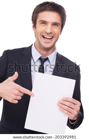 Look at this! Happy young man in formalwear holding blank paper and pointing it with smile while standing isolated on white background