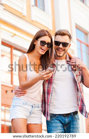 Look at this picture! Low angle view of beautiful young loving couple standing outdoors together and looking at the mobile phone - stock photo