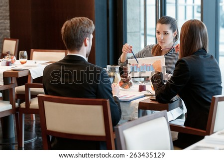Look at this trend. View on the group of business managers discussing charts and diagrams during business lunch in restaurant - stock photo