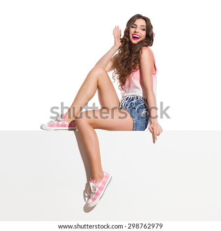 Look Below Me. Laughing young woman in pink top, jeans shorts and pink sneakers sitting on the white banner and pointing down. Full length studio shot isolated on white. - stock photo