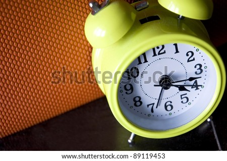 look down on green alarm clock with color background - stock photo