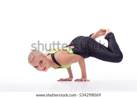 Look easy, huh? Portrait of a beautiful female gymnast doing a handstand balancing gracefully on her arms smiling to the camera isolated