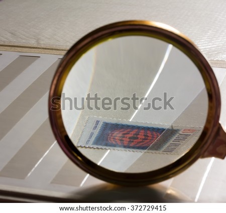 Look for the stamp in the white stamp-album through a magnifying glass. The concept of philately and collecting, selective focus - stock photo