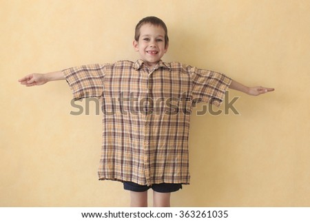 look forward to adult life. boy in daddy's shirt which is too big for him. the concept of growth and getting closer to adulthood - stock photo