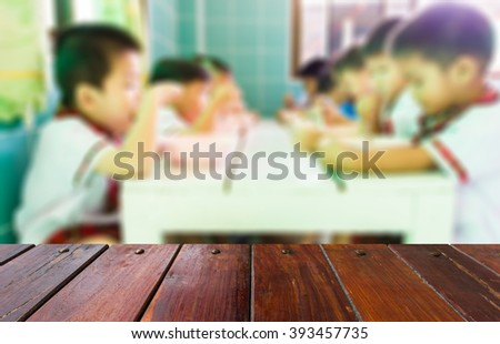 Look from the table, blur image of kindergarten children eating as background.