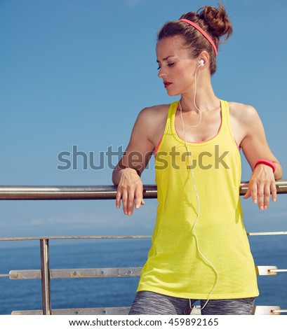 Look Good, Feel great! young healthy woman in fitness outfit relaxing after workout at the embankment