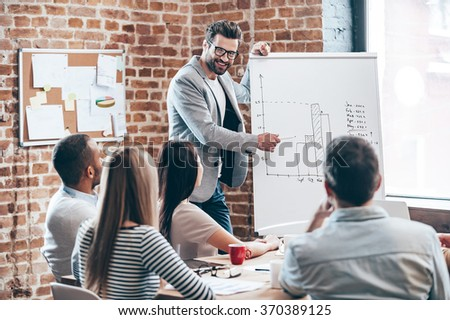 Look how fast growth our company! Handsome young man in glasses standing near whiteboard and pointing on the chart while his coworkers listening and sitting at the table  - stock photo