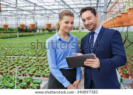 Look, our rating is getting higher. Pleasant content businesspeople holding tablet and looking at it while standing in their greenhouse