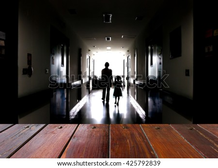 Look out from the table, blur image of a mother and daughter walking on the dark corridor in the hospital. - stock photo