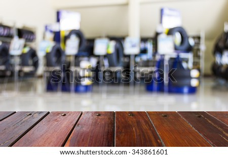 Look out from the table, blur image of shop and tire repair services as background. - stock photo
