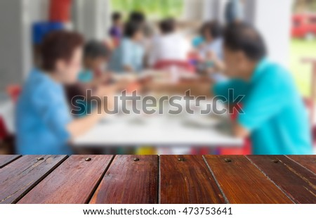 Look out from the table, blur image of the family dining as background.