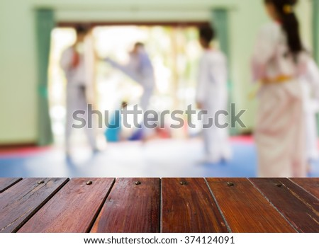 Look out from the wooden table, Blur image of taekwondo class as background.