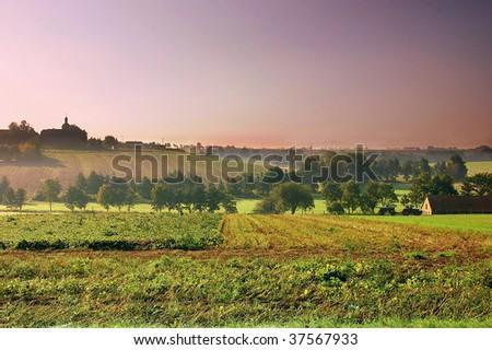 Look over fields to the village church in Göhren - stock photo