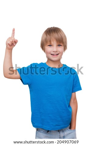 Look over there. Cheerful little boy pointing up and smiling while standing isolated on white - stock photo