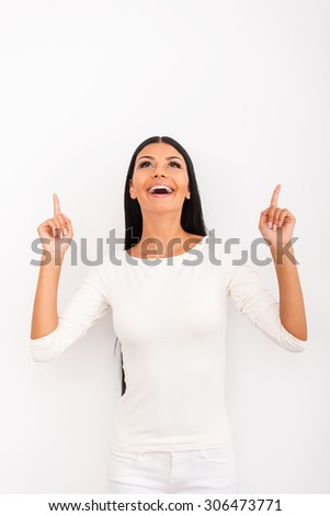 Look over there! Cheerful young woman pointing up while standing against white background - stock photo