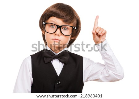 Look over there! Cute little boy pointing up and looking at camera while standing isolated on white - stock photo