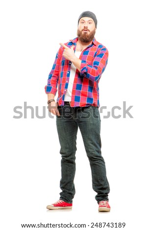 Look over there! Full length of surprised bearded young man in casual wear pointing copy space and smiling while standing isolated on white background - stock photo