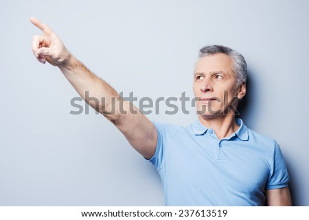 Look over there! Handsome senior man pointing away while standing against grey background