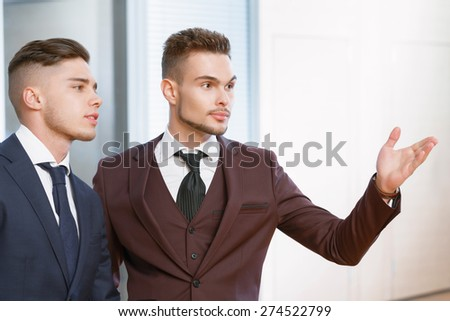 Look there. Young handsome businessman showing something to his colleague pointing with his hand - stock photo