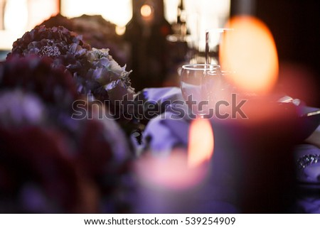 Look through burning candles at rich dinner table