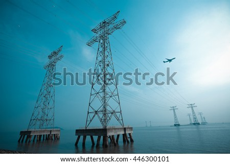Look up at High-voltage power transmission towers in the sea skyline - stock photo