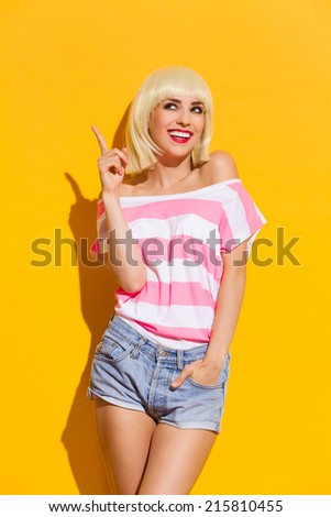 Look up there. Smiling beautiful blonde young woman pointing up.  - stock photo