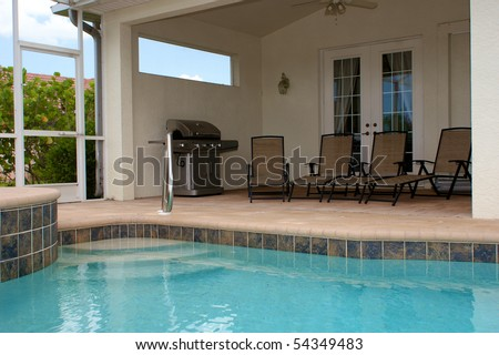 looking across a large built in pool to a sitting are with gas grill and four lounge chairs - stock photo