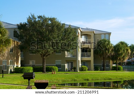 Looking across pond at three story apartment complex in naples florida. - stock photo