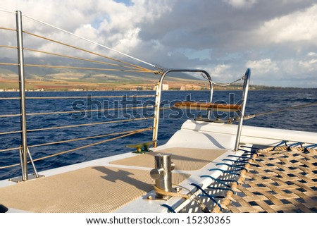 Looking across the bow of a catamaran sailboat, with island on horizon - stock photo