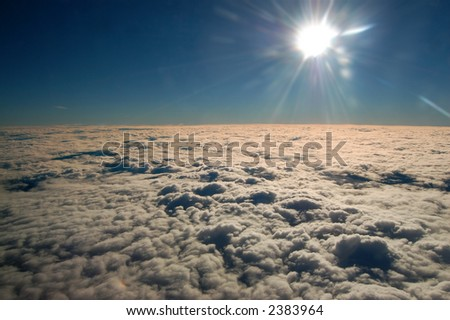 looking across the clouds into the afternoon sun - stock photo