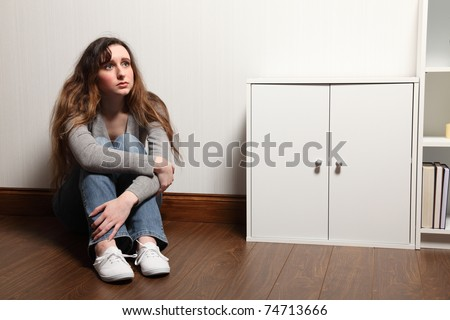 Looking anxious and scared a teenage girl sitting alone on the floor at home, looking upward. - stock photo